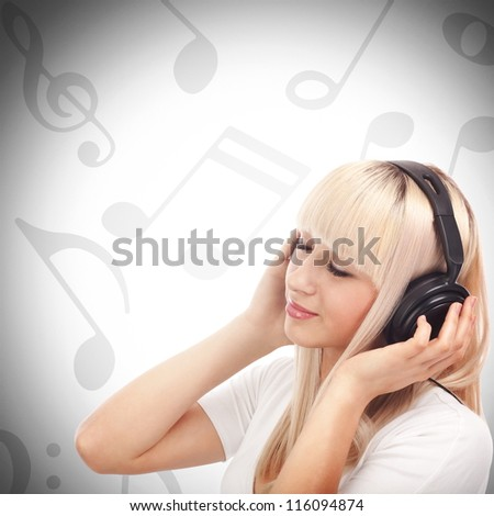 Pretty young girl enjoys listening music between musical notes - stock photo