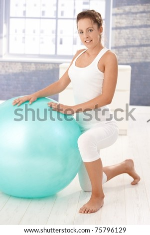 Pretty young girl exercising with fitball at home, smiling.?