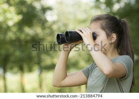 Pretty young girl exploring the environment with a binocular  - stock photo