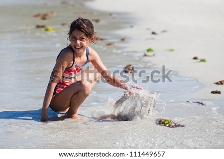 pretty young girl having fun by playing at the beach