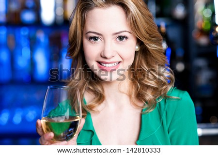 Pretty young girl having wine at a bar