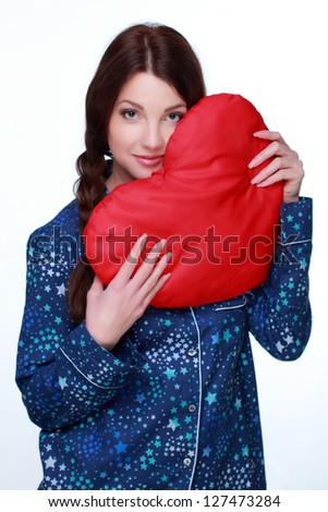 Pretty young girl holding a big heart symbol on white background on Holiday theme