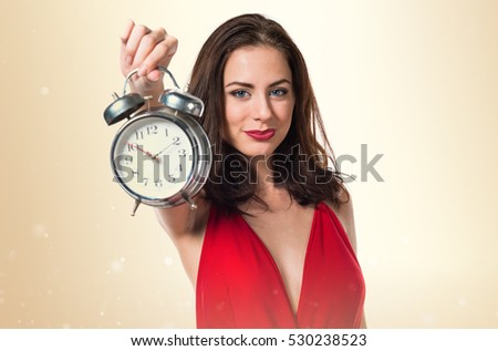 Pretty young girl holding vintage clock on ocher background