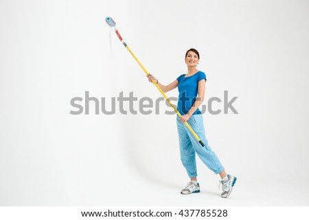 Pretty young girl in blue t-shirt and jeans painting the wall in white color with roller, looking at camera, over white background. - stock photo