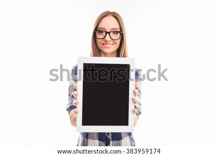 Pretty young girl in checkered shirt and glasses showing screen of tablet