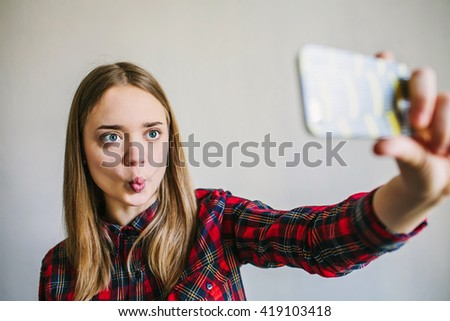 Pretty young girl in plaid shirt taking selfie and making duck face. - stock photo