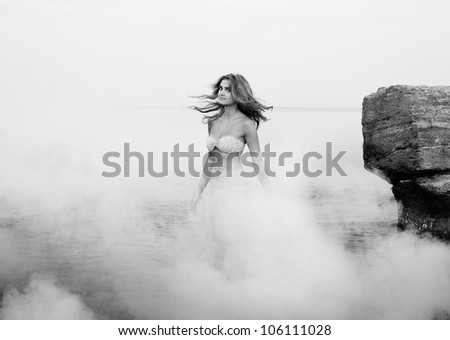 Pretty young girl in the morning sea, black and white - stock photo