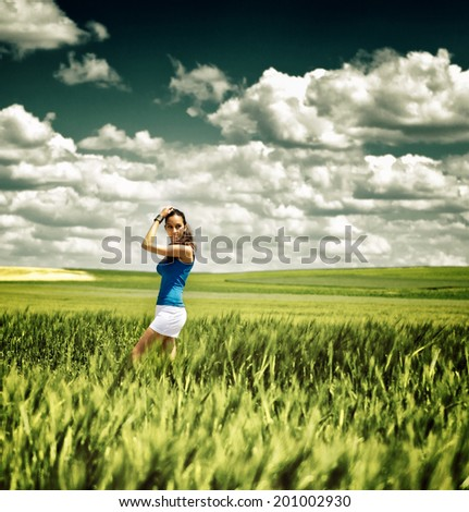 Pretty young girl in white summer shorts standing sideways in a green wheat field under a dramatic sky with clouds , toned effect in square format