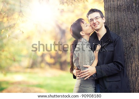 Pretty young girl kisses in cheek her boyfriend in the park; autumn leaves and sunbeams on the background; there is a heart carved on the tree behind - stock photo
