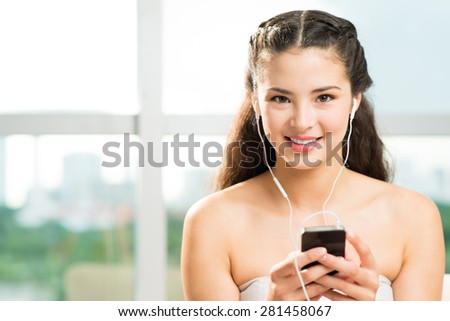 Pretty young girl listening to the music on her smartphone