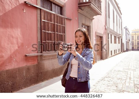 Pretty young girl looking at her camera in a narrow street with old pink buildings behind her in casual jeans and denim jacket