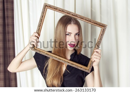 Pretty young girl looking through picture frame - stock photo