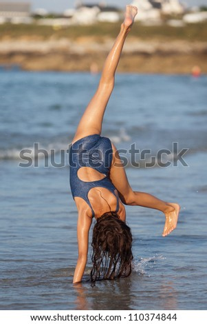 pretty young girl makes a handstand at the beach - stock photo