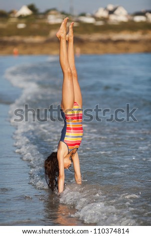 pretty young girl makes a handstand in the surf of the sea - stock photo