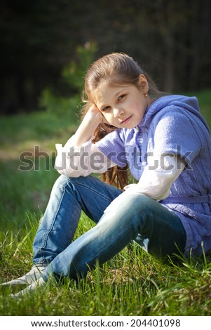 Pretty young girl on Fresh spring grass - stock photo