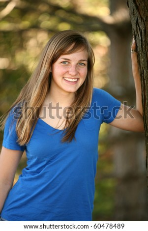 pretty young girl outside by tree smiling