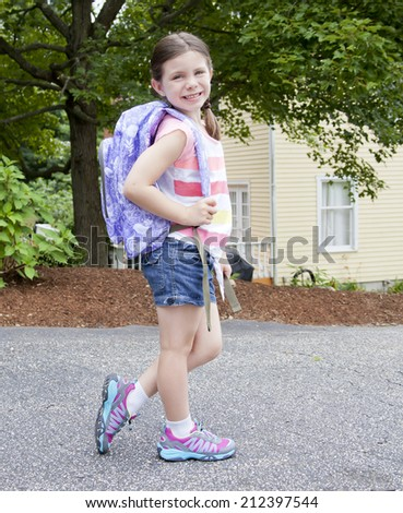 Pretty young girl portrait outdoors with a backpack - stock photo