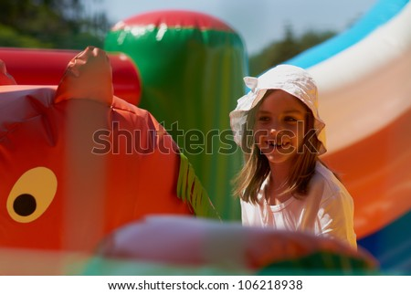 Pretty young girl posing in a bouncing castle in a bright sunny day with beautiful smile - stock photo