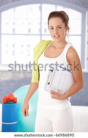 Pretty young girl prepared for personal training in gym, holding her training plan in hand.? - stock photo