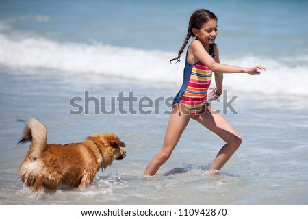 pretty young girl runs with her Elo puppy through the sea water - stock photo