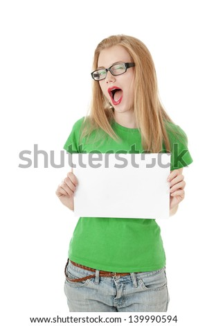 Pretty young girl showing empty blank  paper sign for text. Cute girl wearing glassed and green tee-shirt on white background. - stock photo