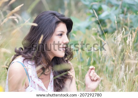pretty young girl sitting in a field with a dandelion in her hand selective focus - stock photo