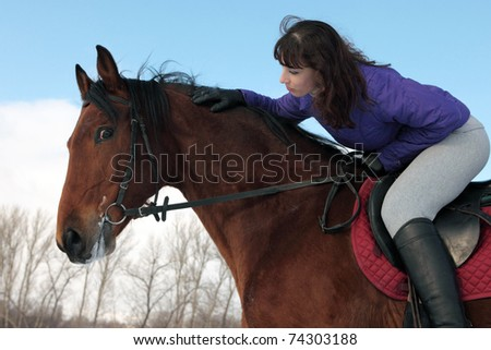 Pretty young girl, sitting on a bay horse, leaning forward to its mane.