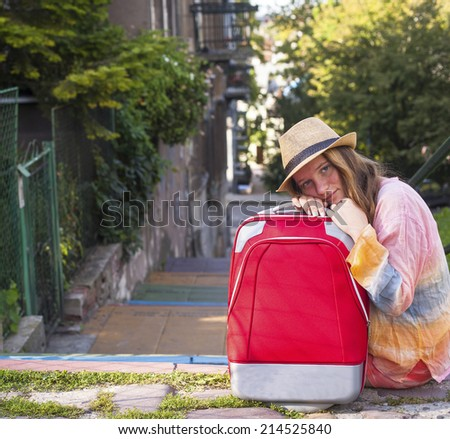 Pretty young girl sitting on the streets of European cities with the red suitcase. Travel concept. - stock photo