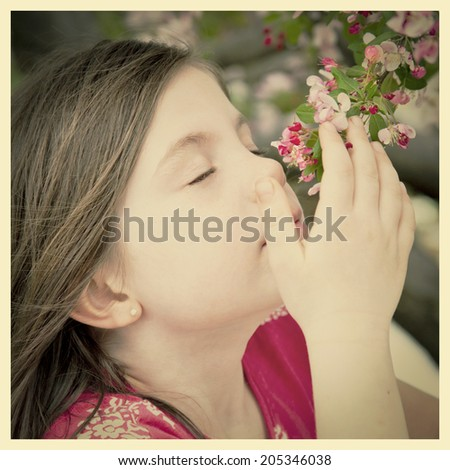 Pretty young girl smelling the blossoms with instagram effect - stock photo