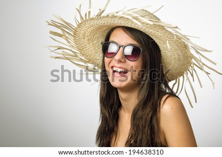 Pretty young girl smiling with straw hat and sun glasses in the studio - stock photo