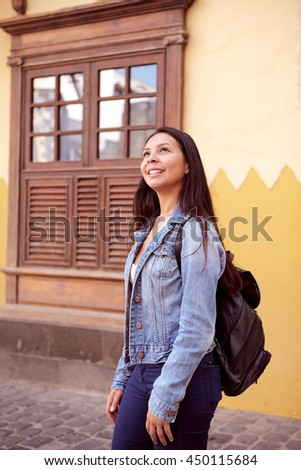 Pretty young girl standing, looking up with a toothy smile and her hair loose wearing casual clothing with an old building behind her
