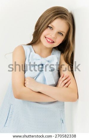 Pretty young girl standing near white wall in blue dress with big bow - stock photo