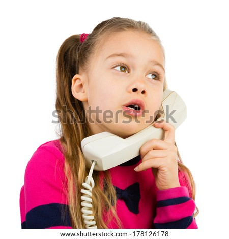 Pretty young girl talking by the corded telephone, isolated - stock photo