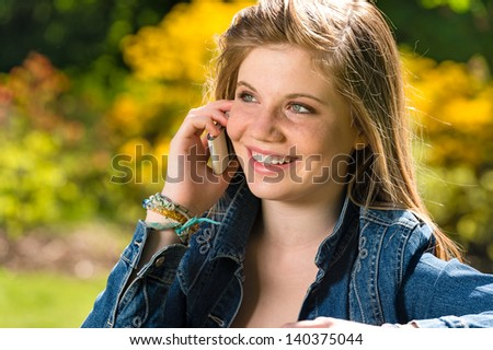 Pretty young girl talking on the phone in the park - stock photo