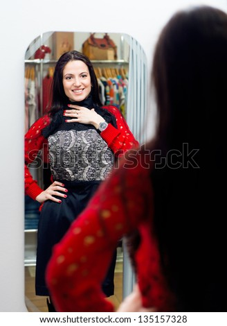 Pretty young girl trying new dress in fitting room - stock photo
