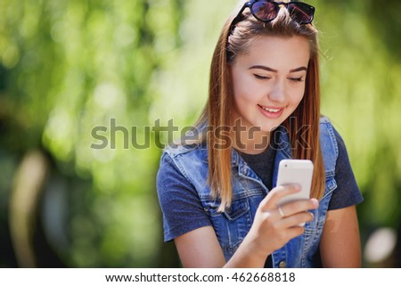 Pretty young girl typing on the smart phone in a park with a green unfocused background.