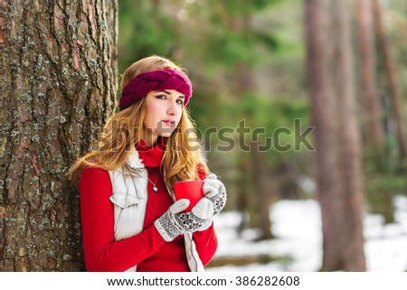 Pretty young girl walking in winter forest. Happy girl in red pink Headband drink  tea or coffee in red cup because its very cold weather