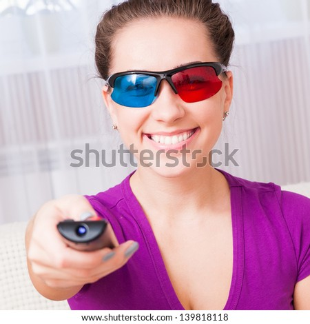 pretty young girl watching 3d television at home - stock photo