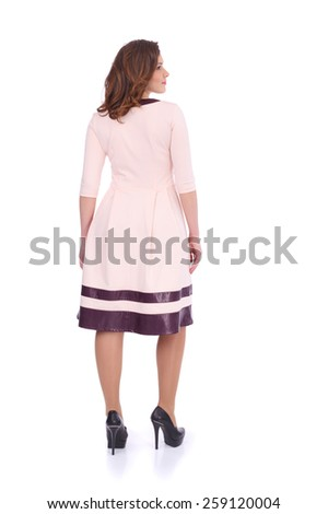 pretty young girl wearing a pink dress, back view