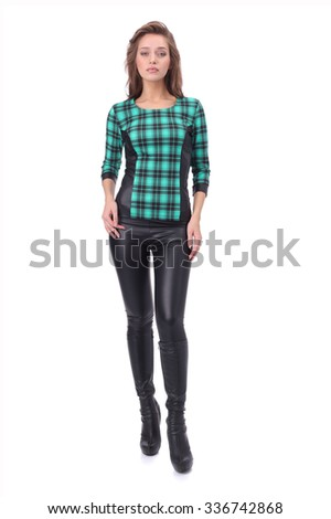 pretty young girl wearing green checked top and black leather trousers - stock photo