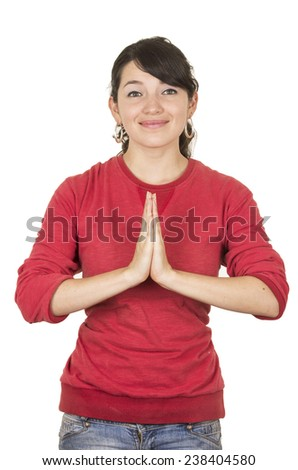 pretty young girl wearing red top posing with palms together gesturing praying isolated on white - stock photo