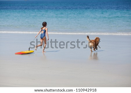 pretty young girl with a surfboard and her cute Elo puppy running at the beach to the water - stock photo