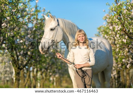 Pretty young girl with a white horse in blooming garden
