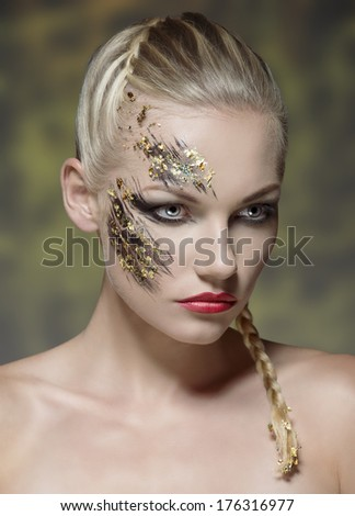 pretty young girl with blonde bride hair-style and naked shoulders posing with creative strong make-up on her perfect visage
