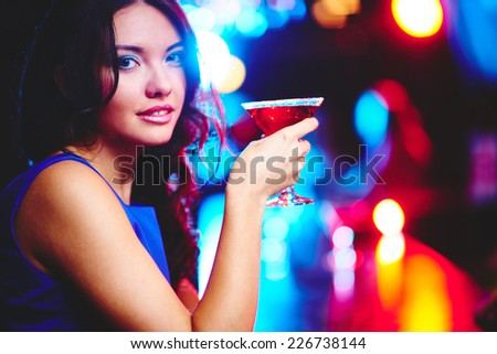 Pretty young girl with cocktail looking at camera on sparkling background - stock photo