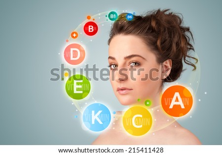 Pretty young girl with colorful vitamin icons and symbols on gradient background - stock photo