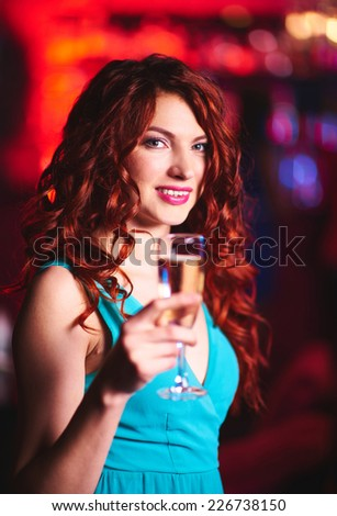 Pretty young girl with flute of champagne looking at camera