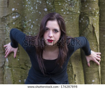 Pretty Young Girl with Intense Expression in Front of Tree - stock photo