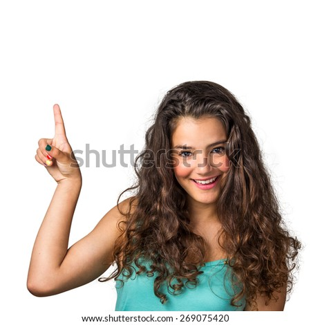 Pretty young girl with joyful expression pointing her finger up  - stock photo