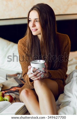 Pretty young girl with long hairs   enjoying morning time , eating  apples and cookies, drinking tea or coffee , warm cozy colors. Fall or winter time  concept.  - stock photo